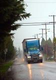 Blå modern halv lastbil med hightlight på att regna vägen Royaltyfri Fotografi