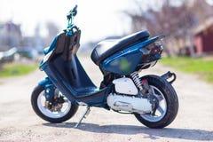 Blå modern sparkcykel på grusvägen Arkivbild