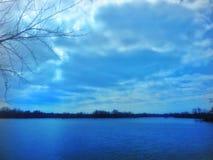 Blå molnig dag på sjön arkivbilder