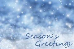 Blå mousserande julbakgrund, snö, text kryddar hälsningar Arkivfoton
