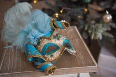 Blå och guld- karnevalmaskering som ligger på en trästol royaltyfria bilder
