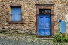 Blå och sliten dörr för gräns - och fönster på stenväggarna av en sma Royaltyfri Bild