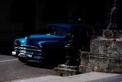 Blå oldtimer som bryter ut ur mörkret arkivfoto
