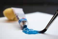 Blå olje- målarfärg, rör och borste på vitbok royaltyfria foton