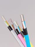 Blå optisk kabel för fiber med avrivna och utsatta fibrer framme av andra kablar Arkivfoton