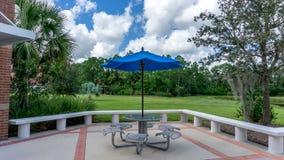 Blå paraply- och metallståltabell av kafeterian av en tillståndshögskola i Florida, USA arkivfoton