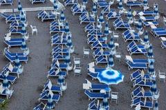 Blå paraplyer och schäslong på den tomma sandiga stranden, Amalfi, Italien Royaltyfri Bild