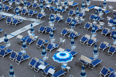 Blå paraplyer och schäslong på den tomma sandiga stranden, Amalfi, Italien Royaltyfria Foton