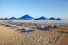 Blå paraplyer och schäslong på den tomma sandiga stranden, Grekland Royaltyfri Fotografi