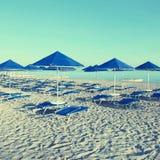 Blå paraplyer och schäslong på den tomma sandiga stranden, Grekland Arkivbilder