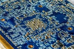 Blå PCB för strömkretsbräde med många mikroskopiska elektroniska delar Arkivbild
