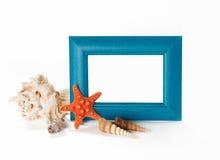 Blå photoframe med snäckskal near det Arkivbild