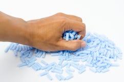 Blå plast- pärla i mänsklig hand Royaltyfria Foton