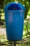 Blå plast- soptunna på en trädgård arkivfoton