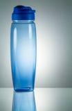 Blå plast- vattenflaska med reflexion på vitt upplyst b Royaltyfria Bilder