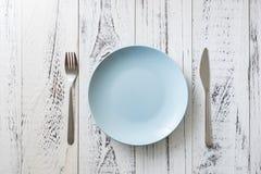 Blå platta på vit träbakgrund med redskap arkivfoto