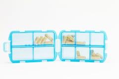 Blå preventivpillerask med preventivpillerar på vit bakgrund Royaltyfria Bilder