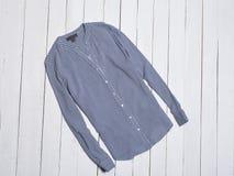 Blå randig bomullsskjorta på vit träbakgrund för begreppsframsida för skönhet blå ljus kvinna för makeup för mode fotografering för bildbyråer