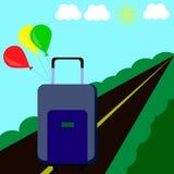 Blå resväska med kulöra bollar på bakgrunden av vägen, solen och molnen Arkivfoton