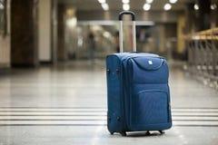 Blå resväska på flygplatsen arkivfoto