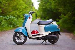 Blå retro sparkcykel i skogen med hjälmen Arkivfoton