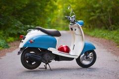 Blå retro sparkcykel i skogen med hjälmen Royaltyfri Fotografi