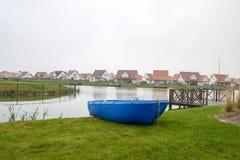 Blå roddbåt på sjön på semester Arkivbild