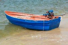 Blå roddbåt på stranden Arkivfoton