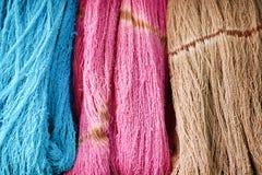 Blå, rosa och brun bakgrund, mönstrar den färgrika naturen av den mångfärgade för trådtextur för rå bomull gruppen royaltyfria foton