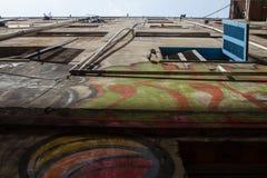 Blå rullgardin för öppet fönster på den sjaskiga väggen med rör Arkivfoto
