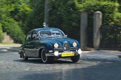 Blå SAAB bil på det retro spåret för springa för bilar Arkivfoton