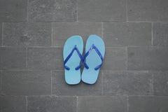 Blå sandal på tegelstengolv Royaltyfri Foto