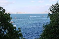 Blå sikt av havet mellan gröna buskar I vatten vilar folket på katamaran, fartyg och fartyg Royaltyfri Foto