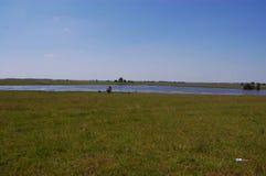 Blå sjö mellan två kuster Arkivfoto