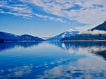 Blå sjö och blåa snöig berg Arkivfoto