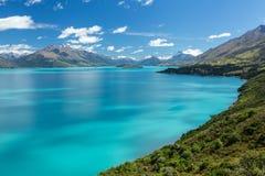Blå sjö som omges av berg Royaltyfria Bilder