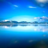 Blå sjösolnedgång- och himmelreflexion på vatten Versilia Tuscany, Arkivbilder