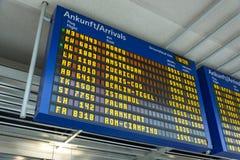 Blå skärm med ankomster på flygplatsen i tyskt och engelskt royaltyfria bilder
