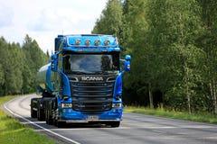 Blå Skåne R580 behållarelastbil på den lantliga vägen Arkivfoto
