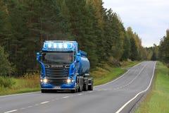 Blå Skåne R580 behållarelastbil på den lantliga vägen Fotografering för Bildbyråer