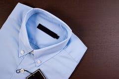 Blå skjorta med svartmellanrumsprislappen royaltyfria bilder