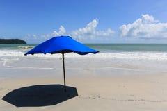 Blå slags solskydd på en öde strand Royaltyfria Foton