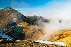 Blå smaragdsjösikt och aktiv vulkan som röker sulphur från overklig vulkanisk terräng, Tongariro nationalpark, Nya Zeeland arkivfoto