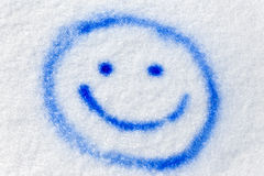Blå smiley som besprutas i snön Arkivfoto