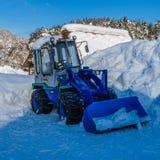 Blå snötraktor med kedjan på stora hjul Fotografering för Bildbyråer