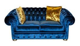 Blå soffa med isolerade gulingkuddar Arkivbilder