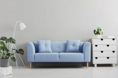 Blå soffa mellan den vita lampan och kabinettet i grå vardagsrum int arkivbild