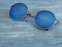 Blå solglasögon på en träbakgrund Royaltyfria Foton