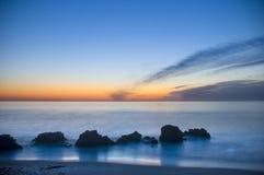 Blå soluppgång på stranden arkivbild