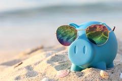 Blå spargris med solglasögon på havsstranden, sparande planläggning fo royaltyfria foton